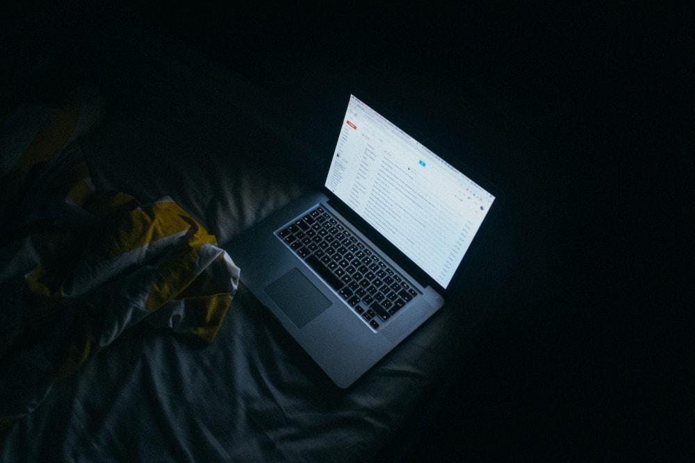 MacBook im dunkeln auf dem Bett